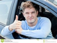 attractive-man-sitting-his-car-thumb-up-15519060.jpg